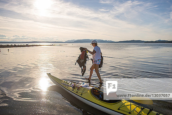 Mature female kayaker carrying life jackets from kayak  Quadra Island  Campbell River  Canada