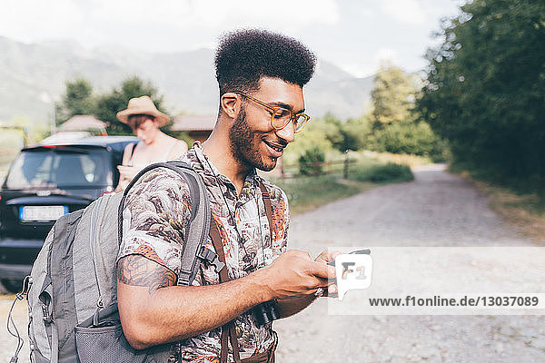 Young male hiker on dirt track looking at smartphone    Primaluna  Trentino-Alto Adige  Italy