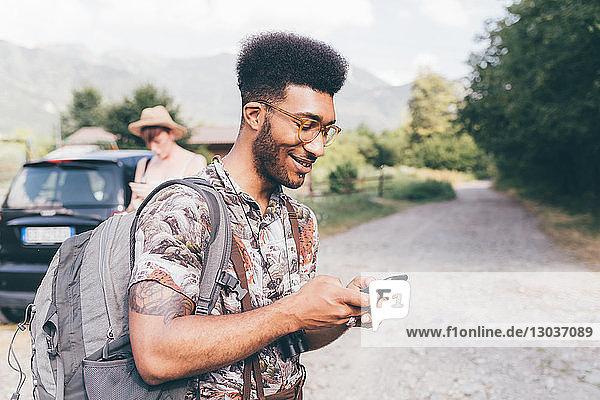 Junger männlicher Wanderer auf Feldweg mit Blick auf Smartphone    Primaluna  Trentino-Südtirol  Italien