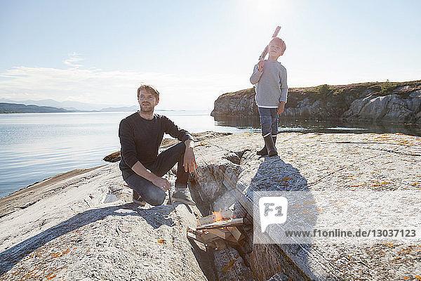 Junge und Vater am Lagerfeuer am Einlauffelsen  Aure  More og Romsdal  Norwegen