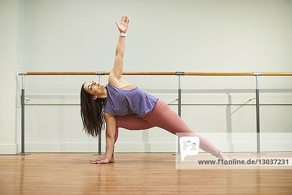 Full length shot of a single young woman doing yoga indoors
