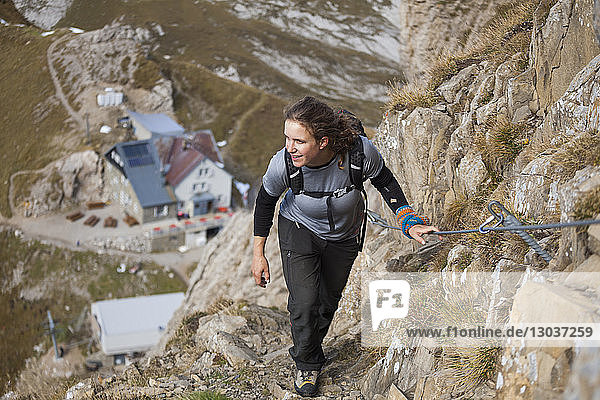 A woman hikes up the Lisengrat (Lisen Ridge) trail  Alpstein  canton of St. Gallen  Switzerland. The guesthouse on Rotsteinpass is visible in the background.