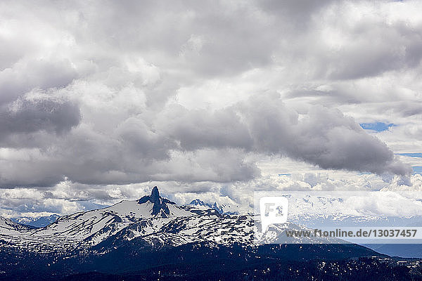 Black Tusk  an extinct Strato Volcano and iconic peak in Garibaldi Provincial Park stands tall among surrounding mountains as seen on a stormy day from the top of Whistler Blackcomb Ski Resort  British Columbia  Canada