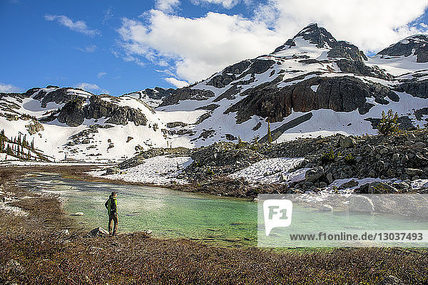 A man stands on the side of a river and looks up at Locomotive Mountain. This is a popular area for backpacking due to its beautiful views and relatively easy access from a logging road †Pemberton  British Columbia  Canada