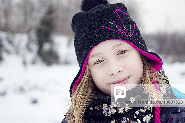 Outdoor headshot portrait of a smiling girl wearing warm winter clothing