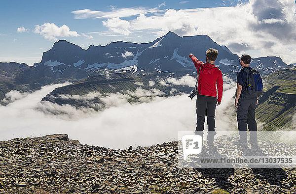 Rear view shot of two adventurous hikers pointing to the mountain†Dyrfjoll †Borgafjordur†Eystri  Iceland