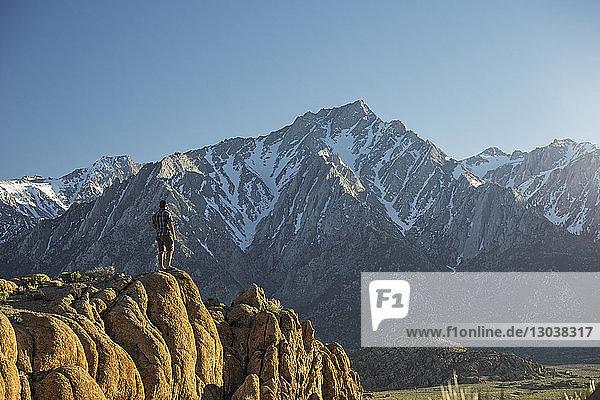 Wanderer in voller Länge mit Blick auf die Aussicht  während er auf einem Bergfelsen steht
