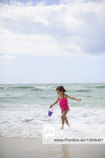 Girl playing on beach with bucket against cloudy sky