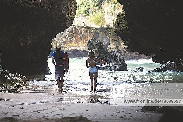 Rückansicht von Freunden  die beim Strandspaziergang an Felsformationen ein Surfbrett tragen