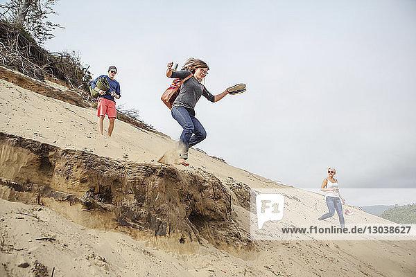 Frau springt von Sanddüne und genießt mit Freunden am Strand