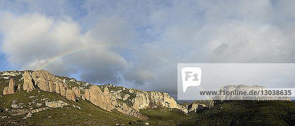 Idyllischer Blick auf Regenbogen über Berge vor bewölktem Himmel