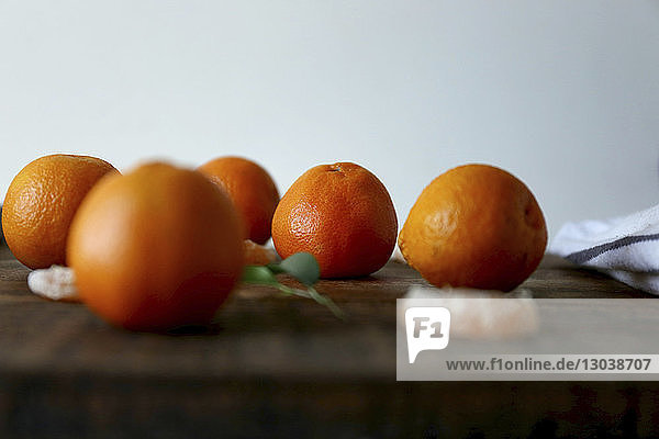 Close-up of oranges on wooden table against white background