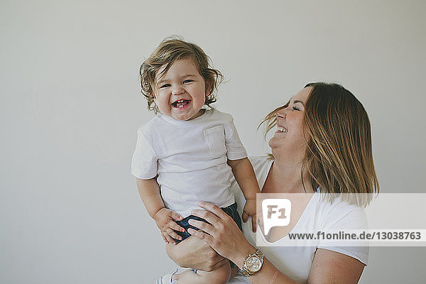 Portrait of cheerful son being carried by mother against wall at home