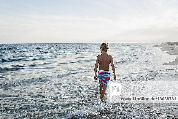 Rear view of shirtless boy walking at Tobay Beach in waves against sky