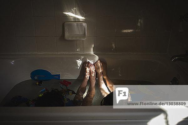 Hochwinkelansicht von Geschwistern beim Spielen in der Badewanne