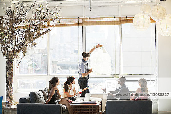 Businessman showing blueprint to colleagues during meeting in creative office