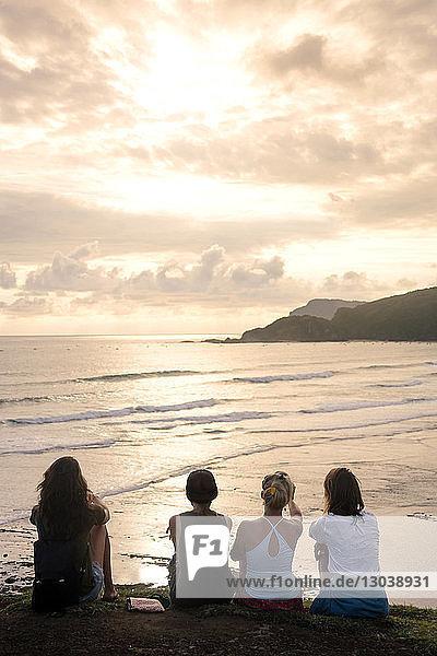 Rückansicht von Freundinnen  die bei Sonnenuntergang am Strand vor bewölktem Himmel sitzen