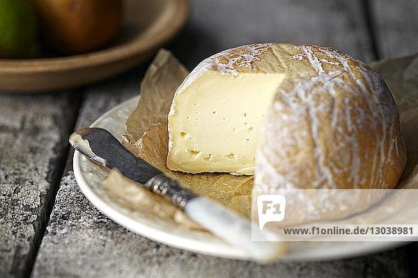 Nahaufnahme von Käse mit Messer im Teller auf dem Tisch