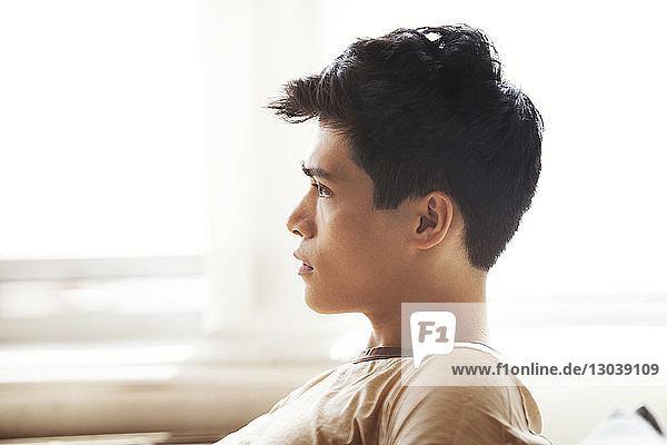 Seitenansicht eines nachdenklichen Mannes  der zu Hause am Fenster sitzt