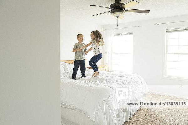 Geschwister halten beim Springen auf dem Bett Händchen