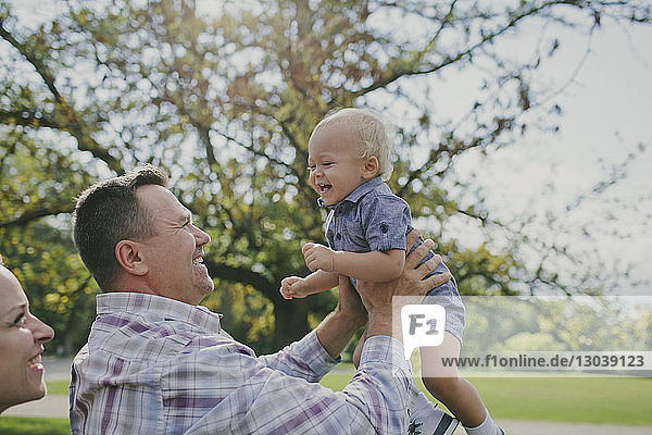 Glücklicher Mann hebt kleinen Jungen an  während er mit Frau im Park steht