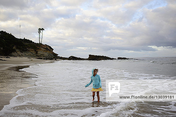 Girl playing in waves at Laguna Beach against cloudy sky