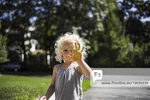 Verspieltes Mädchen  das im Rasen stehend eine bemalte Hand zeigt