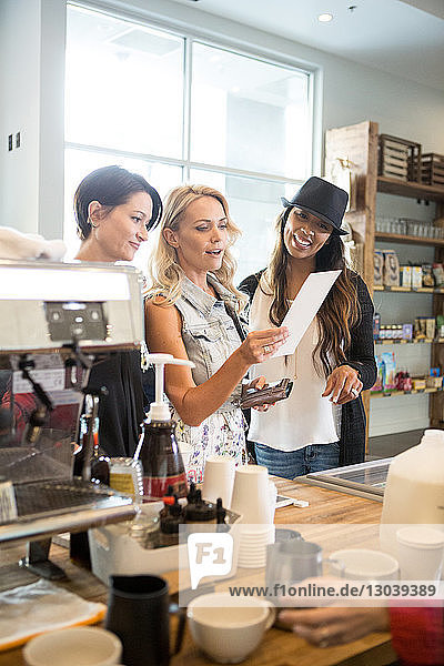 Happy female friends reading menu while standing at counter in cafeteria