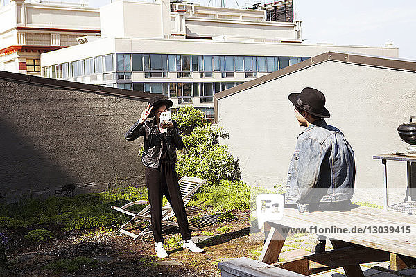 Glückliche Frau gestikuliert Siegeszeichen  während sie einen Mann durch eine Sofortbildkamera auf der Terrasse fotografiert