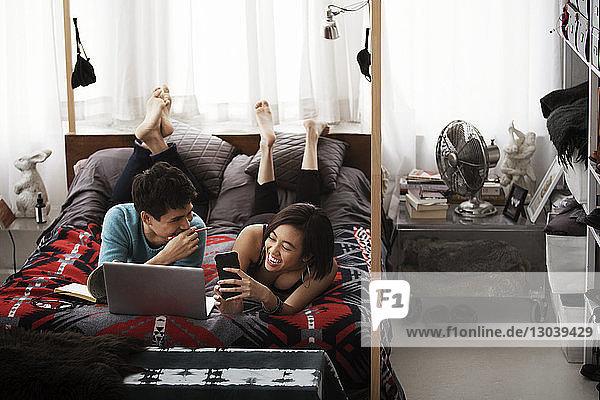 Fröhliches Paar benutzt Laptop  während es zu Hause auf einem Himmelbett liegt
