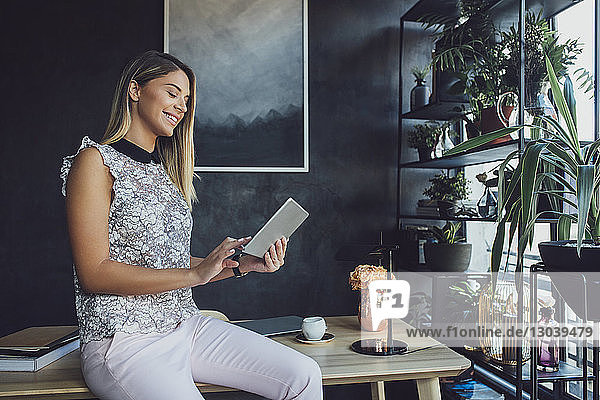 Smiling businesswoman using tablet computer while sitting on table in home office