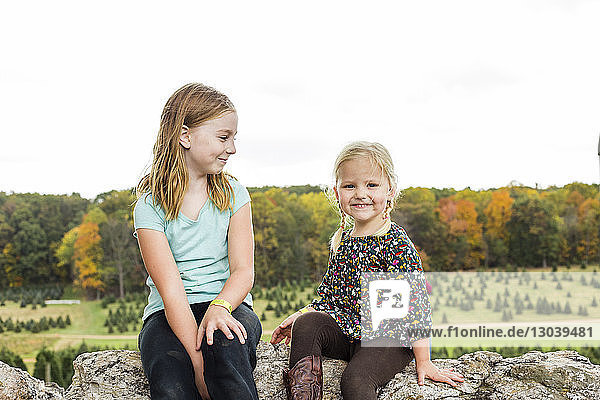 Portrait of smiling girl sitting by sister on rock against clear sky