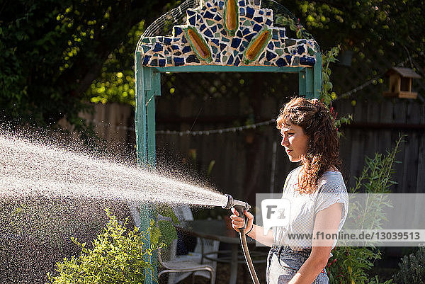 Side view of woman watering in garden using hose pipe