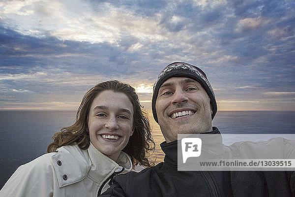 Porträt eines glücklichen Vaters mit Tochter bei Sonnenuntergang am Meer stehend