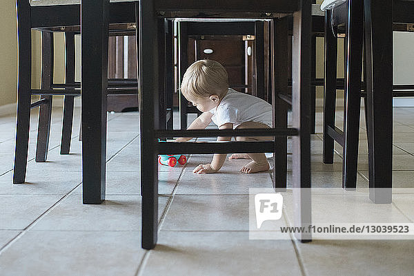 Baby boy playing with toy under dining table at home