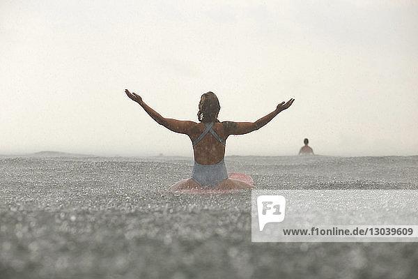 Rückansicht einer Frau mit erhobenen Armen  die während der Regenzeit auf einem Surfbrett im Meer sitzt