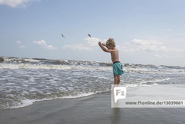 Seitenansicht eines Jungen ohne Hemd  der am Strand gegen den Himmel steht