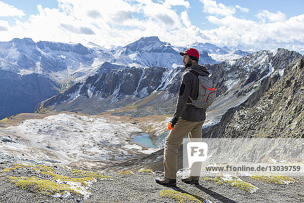 Hiker looking at view while standing on top of mountain