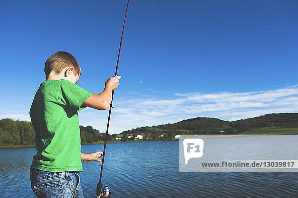 Side view of boy looking at fishing rod while standing against lake