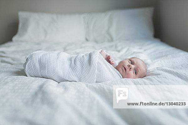 Seitenansicht eines neugeborenen Jungen,  der weg schaut,  während er zu Hause im Bett liegt