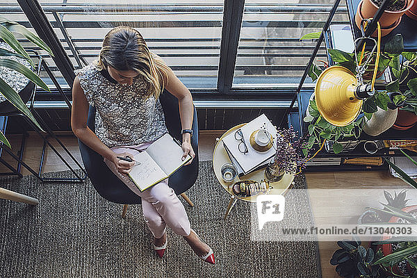 Overhead view of businesswoman writing in diary while sitting on chair at home office