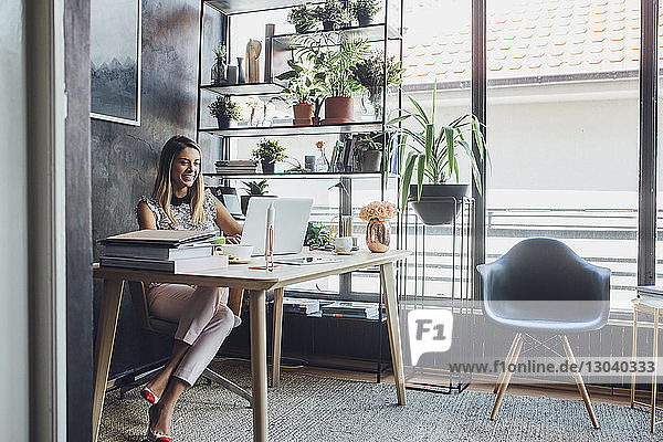 Happy businesswoman working on laptop computer while sitting at table in home office