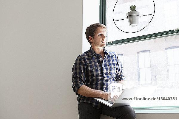 Nachdenklicher Geschäftsmann sitzt mit Laptop auf dem Fensterbrett im Büro Nachdenklicher Geschäftsmann sitzt mit Laptop auf dem Fensterbrett im Büro