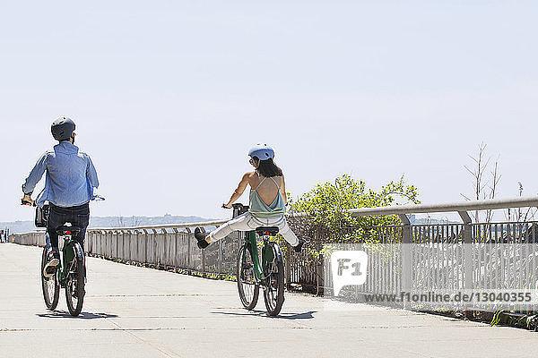 Rückansicht eines Fahrrad fahrenden Paares auf der Promenade bei klarem Himmel