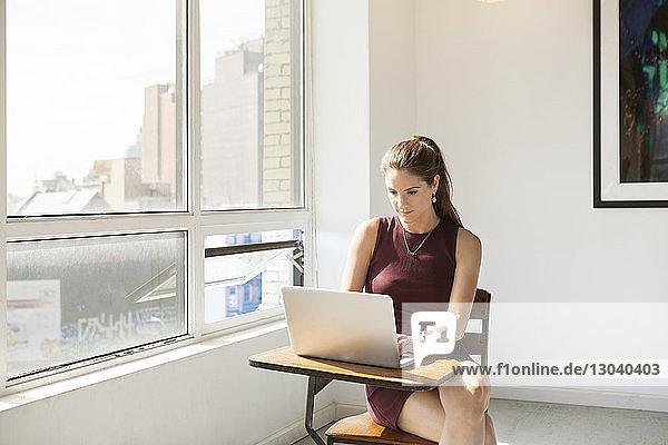 Junge Geschäftsfrau mit Laptop auf dem Tisch im Kreativbüro