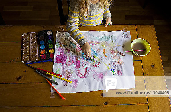 High angle view of girl painting on paper while standing at table