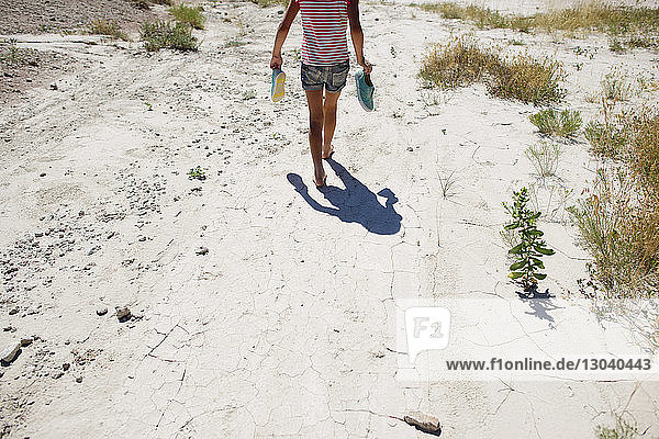 Rear view of girl carrying shoes while walking on field at Badlands National Park