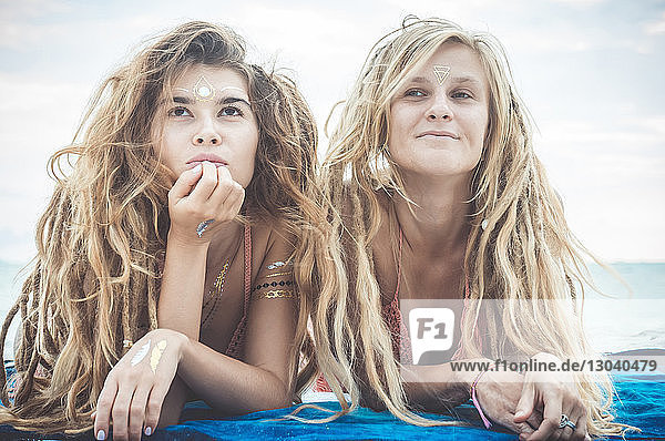 Female friends with dreadlocks relaxing at beach against sky