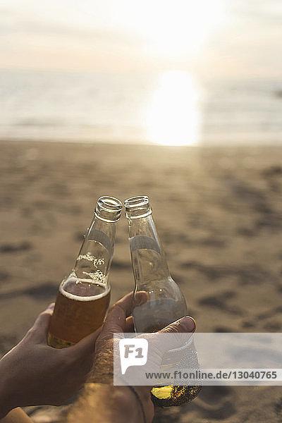 Geschnittene Hände von Freunden  die bei Sonnenuntergang am Strand auf Bier anstoßen