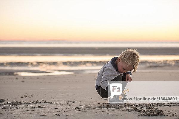Junge spielt mit Spielzeug  während er bei Sonnenuntergang am Strand gegen den Himmel kauert